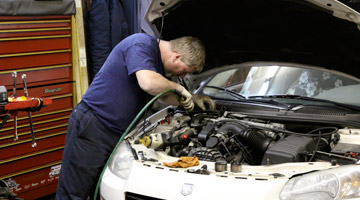 technician servicing a car's electrical systems